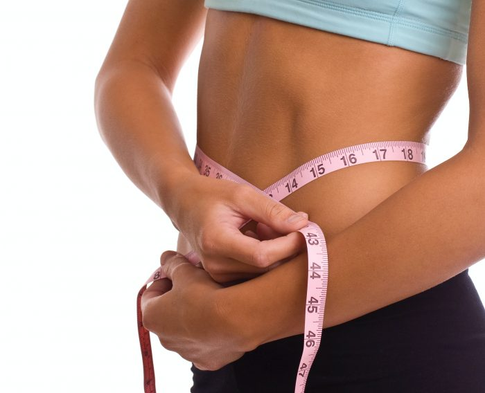 Woman measuring stomach with measuring tape